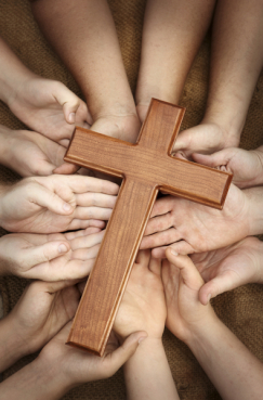 many hands reverently holding a wooden cross