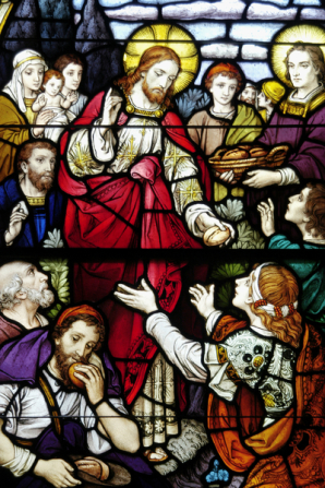stained glass depicting Jesus feeding the poor